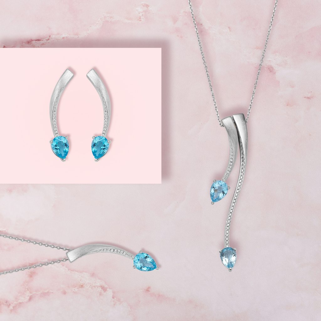 Shooting Star pendants and earrings with blue topaz in white rhodium plate
